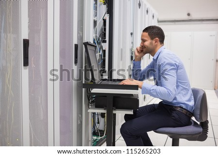 Man maintaining the servers in data center - stock photo