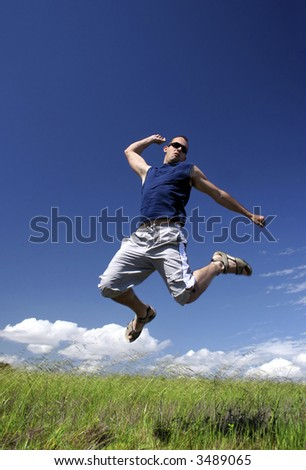 Man make a big jump on a green meadow - stock photo