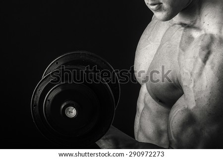 Man makes exercises dumbbells. Sport, power, dumbbells, tension, exercise - the concept of a healthy lifestyle. Article about fitness and sports. - stock photo