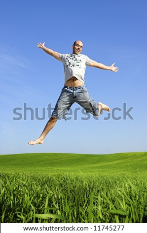 Man making a big jump on a beautiful green meadow - stock photo