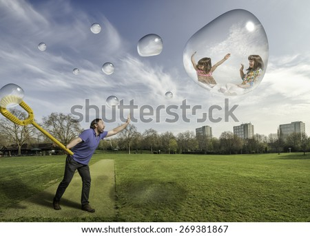 Man making bubbles with his children in a park in a sunny day - stock photo