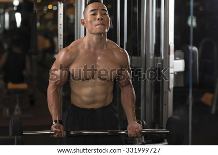 Man making effort to lift heavy barbell - stock photo