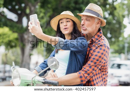 Man making face for selfie with woman on moped in city - stock photo
