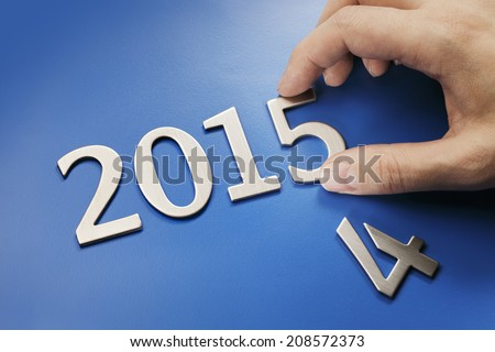 Man making number 2015 from metallic numbers. - stock photo