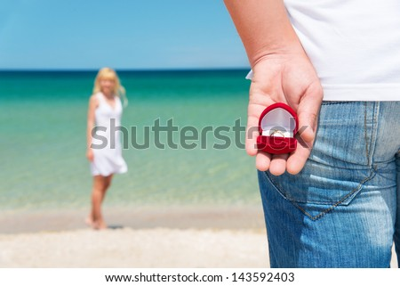 man making proposal with engagement ring and gift box to his woman at sea beach - wedding concept - stock photo