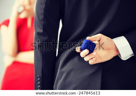man making proposal with wedding ring and gift box. - stock photo