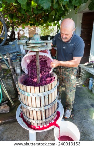 man making red wine with classic press - stock photo