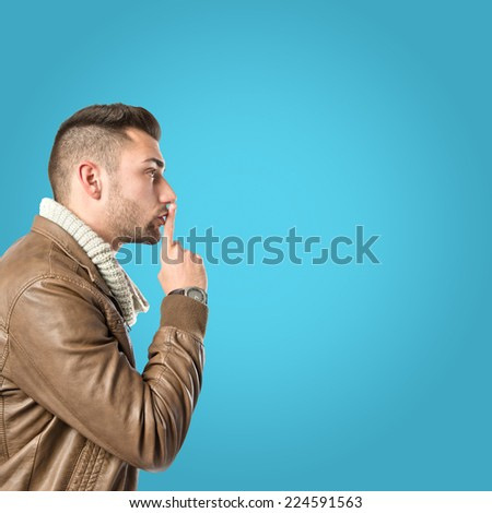 Man making silence gesture over blue background - stock photo