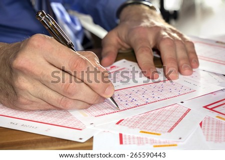 Man Marking on lottery ticket with a pen - stock photo
