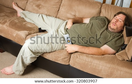 man mat falls asleep on the couch with his hands down his pants - stock photo