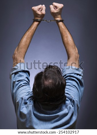 Man, mature, with handcuffs, of backs, arms raised - stock photo