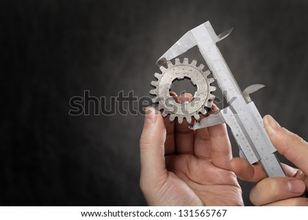 Man measuring the diameter of old cog with vernier caliper. Lots of copy space to the left. - stock photo