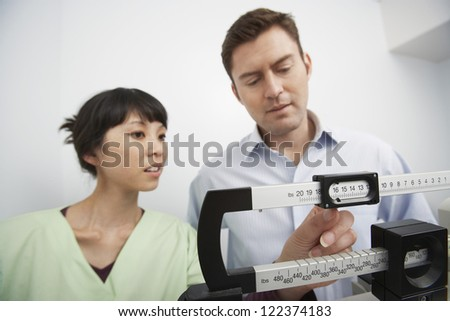 Man measuring weight with doctor adjusting scale - stock photo