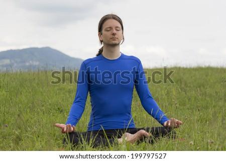 Man meditating in lotus pose during yoga outdoors - stock photo