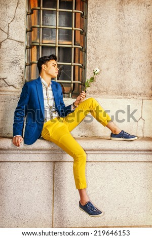 Man Missing You. Dressing in blue blazer, yellow pants, casual sneakers, a young handsome guy is sitting by a window on street, looking down at white rose on hand, thinking. Man Casual Fashion - stock photo