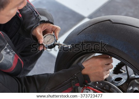 man motorcycle tire manual air pressure testing before traveling trip for safety riding vehicle - stock photo