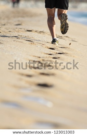 Man muscled legs running on the sand of a beach - stock photo