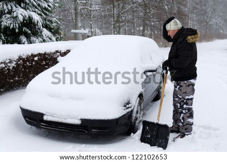 Man need again remove snow from the car - stock photo