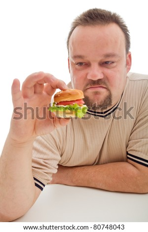 Man not happy about the size of his hamburger - size matters in diet too - stock photo