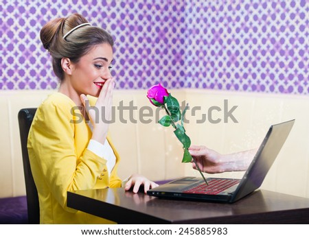 Man offering a rose to a beautiful woman over laptop screen   - stock photo