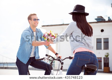 Man offering flowers to charming woman - stock photo