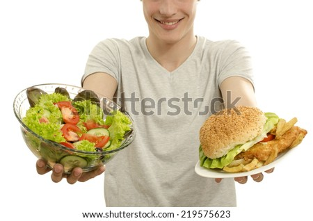 Man offering you a salad and a hamburger. Young man holding in front a bowl of salad and a big burger. Choosing between good healthy food and bad unhealthy food. Fast food versus organic - stock photo