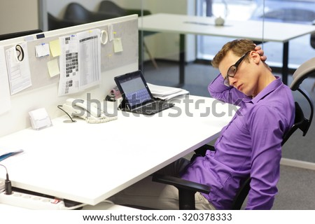 man office worker relaxing neck during work with tablet in his office - stock photo