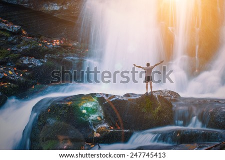 Man on a Great waterfall in a Carpathian mountains. Ukraine - stock photo