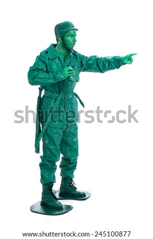 Man on a green toy soldier costume with riffle poiting with his forefinger  isolated on white background. - stock photo