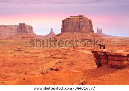 Man on a horse, view from John Ford's Point in Monument Valley with the West Mitten Butte and the Merrick Butte in Utah-Arizona border, United States of America. - stock photo
