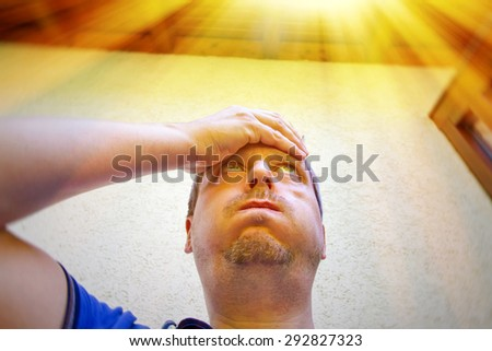 Man on a hot summer day in front of his house - stock photo