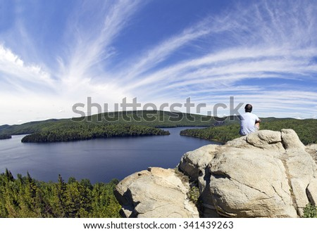 man on a mountain watching the beauty of nature - stock photo