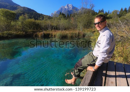 Man on a peer dipping his bare feet into the lake - stock photo