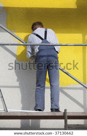 man on a scaffold painting houser with roller - stock photo