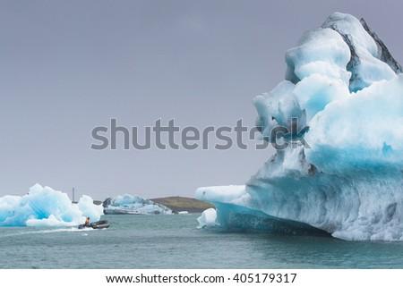Man on a small boat in Jokulsarlon Glacial Lagoon near Vatnajokull in south coast of Iceland - stock photo