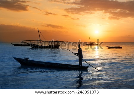 Man on a traditional boat off the coast of Zanzibar at sunset - stock photo