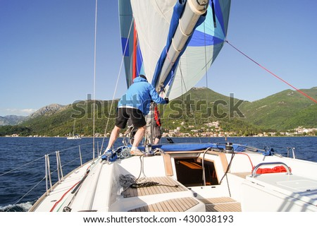 """Man on a yacht sailing in the yards. Tivat, Montenegro - 26 April, 2016. Regatta """"Russian stream"""" in God-Katorskaya bay of the Adriatic Sea off the coast of Montenegro. - stock photo"""
