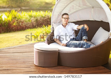 man on an outdoor bed in summer - stock photo