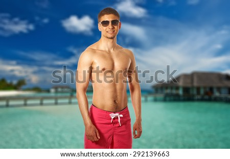 Man on beach with water bungalows at Maldives. Collage. - stock photo