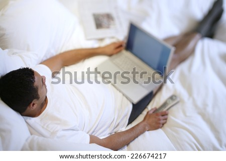 Man on Bed with Laptop - stock photo