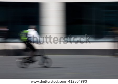 man on bicycle riding through the city, blurred, unrecognizable - stock photo
