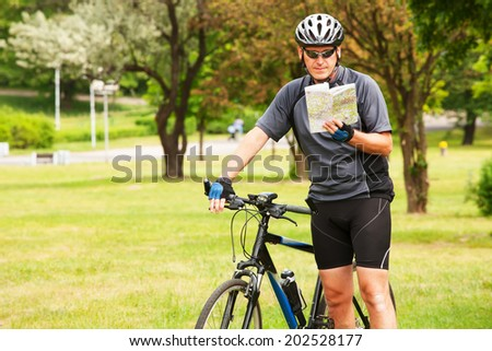Man on bike checking map and looking around.  - stock photo