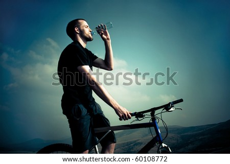 man on bike drink water in front of sky - stock photo