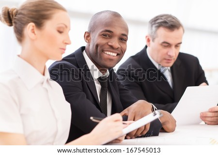 Man on business meeting. Cheerful young African man in formalwear looking at camera and smiling at camera while sitting together with his colleagues - stock photo