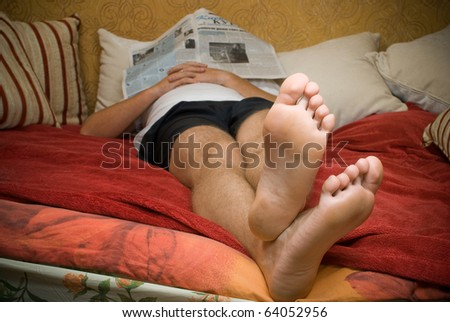 Man on couch reading newspaper - stock photo