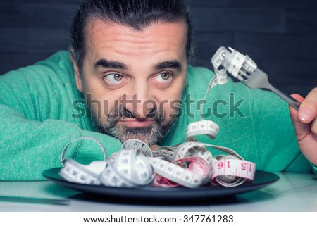 Man on diet, looking unhappy, plate filled with measuring tape instead of food, diet and eating disorder concept - stock photo