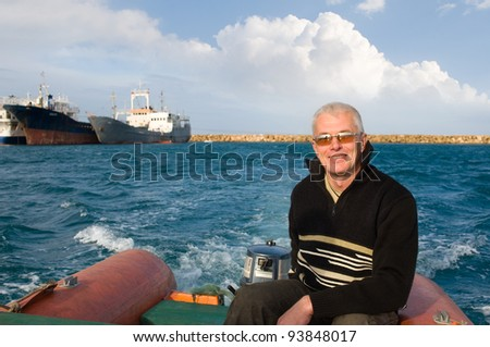 man on inflatable rubber dinghy at sea - stock photo