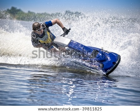 Man on jet ski turns with much splashes - stock photo