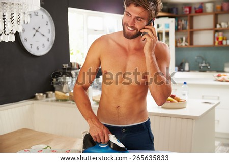 Man On Mobile Phone Standing In Kitchen Ironing Shirt - stock photo