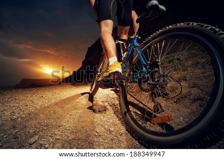 Man on mountain bike rides on the trail on a beautiful sunset. Bicycle wheel closeup. - stock photo
